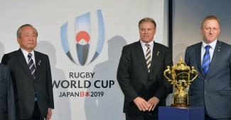 Akira Shimazu (L), chief executive of the Rugby World Cup 2019 organizing committee, World Rugby Chief Executive Brett Gosper (C) and Alan Gilpin, head of the RWC, pose for a photo in London on Oct. 27, 2015, in front of the logo for the 2019 tournament in Japan. (Kyodo) ==Kyodo